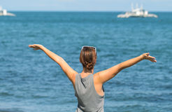 Woman with raised hands on the sea background. Turquoise blue seawater with white boats. Stock Photo