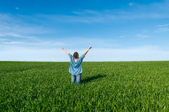Woman with raised hands  standing back in green field Stock Images