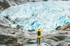 Woman raised hands traveling in Norway. Adventure Lifestyle concept vacations outdoor Nigardsbreen glacier Royalty Free Stock Photos