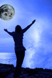 Woman with raised hands a wave and full moon Royalty Free Stock Photography