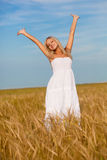 Woman with raised hands on wheat field Stock Photo