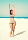 Woman raised her hands up on the beach Stock Images