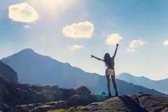 Woman raised her hands up in the mountains Stock Photos