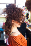 Woman with raised  long curly hair at hairdresser Royalty Free Stock Images
