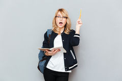 Woman with raised pencil. Woman student wearing glasses raising pencil and opening mouth holding notebook Stock Image