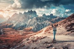 Woman with raised up arms and high mountains at sunset stock photo