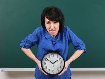 Woman raises a heavy watch, posing by chalk board, time and education concept, green background, studio shot Royalty Free Stock Image