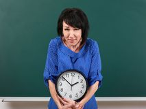 Woman raises a heavy watch, posing by chalk board, time and education concept, green background, studio shot Stock Photography