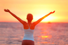 Woman Raising Arms At Beach During Sunset Stock Image