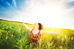 Woman raising arms enjoying sunlight in canola field Royalty Free Stock Photos