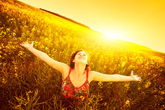 Woman raising arms enjoying sunlight in canola field Stock Photography