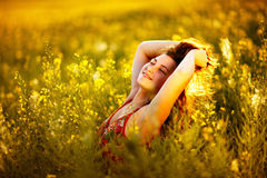 Woman raising arms enjoying sunlight in canola field Royalty Free Stock Photo