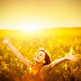 Woman raising arms enjoying sunlight in canola field Stock Photos