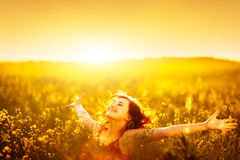 Woman raising arms enjoying sunlight in canola field Royalty Free Stock Images