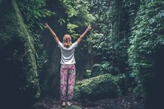 Woman With Raising Arms Facing Pathway Between Forest Trees stock image