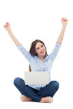 Woman raising arms in front of her laptop. Beautiful young woman over white background Royalty Free Stock Photos
