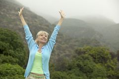 Woman raising arms near forest Royalty Free Stock Image