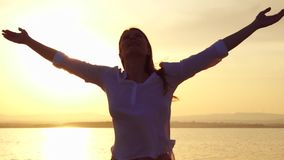 Woman raising arms up at sunset on lake. Female outstretching hands at golden hour in slow motion