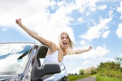 Woman raising hand out of car window Stock Photo