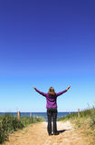 Woman raising hands on a path to the beach Stock Photography