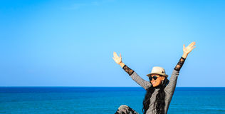 Woman raising hands and smiling at seaside Stock Photos