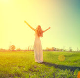 Woman raising hands in sunlight rays. Beautiful woman outdoor raising hands in sunlight rays Royalty Free Stock Photography