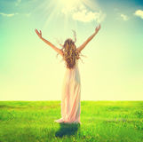Woman raising hands in sunlight rays Stock Photo