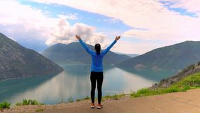 Rear runner posing in mountain area. Woman raising hands on the top of mountain area amazing view on the skyline with rainy clouds and blue water stock footage