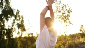 Woman is raising hands up outside in park evening on background of soft sunlight, tracking shot.