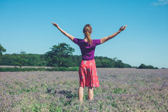Woman raising her arms in a field of purple flowers. A young woman is raising her arms in a field of purple flowers Royalty Free Stock Images