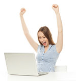 Woman raising her arms in front of laptop. Portrait of a woman over white background Stock Photos