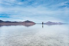 Bonneville Salt Flats, Tooele County, Utah, United States. Woman raising her arms and standing a in crystal clear water with mountains in the background Stock Image