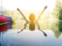 Woman raising her hands in swimming pool Stock Photos