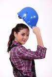 Woman raising her hard hat. Woman raising her blue hard hat Royalty Free Stock Photo