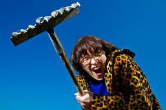 Woman with rake. Yelling woman with rake on  blue background Royalty Free Stock Photos