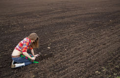 Woman rake on cultivated field black soil Stock Photo