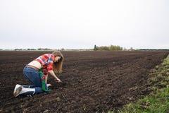 Woman rake on field at black soil Stock Images
