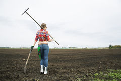 Woman with rake and shovel move away Royalty Free Stock Images