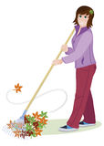 Woman rakes leaves. On the garden in autumn Royalty Free Stock Image