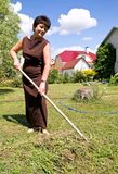Woman rakes up oblique grass Royalty Free Stock Photo