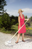 Woman raking the garden path Royalty Free Stock Image