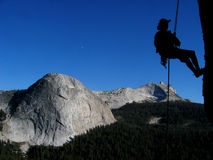 Woman rappelling. Silhouette of a woman rappelling off of Daff dome, Tuolumne Meadows, Yosemite National Park, California with Fairview dome and Cathedral Peak Stock Photography