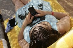 Woman with rasta braids reading sms on beach Stock Photo