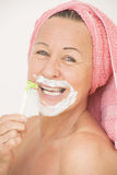 Woman with razor shaving face Royalty Free Stock Photography