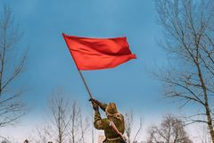 Woman Re-enactor Dressed As Russian Soviet Red Army Soldier Of World War II Waving A Red Flag In Honor Of Victory During stock photography