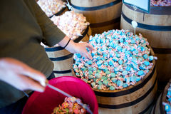A woman reaches for blue salt water taffy in a store. A woman reaches for blue salt water taffy Royalty Free Stock Photo