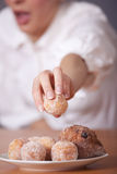 Woman reaches for sugar cake Royalty Free Stock Image