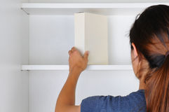 Woman Reaching Into Cupboard Stock Image