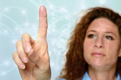 Woman reaching with a finger to touch a screen royalty free stock photo