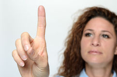 Woman reaching with a finger to touch a screen Royalty Free Stock Image